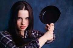 Gek het koken concept Jonge boze huisvrouwenvrouw die slingeren met stock afbeelding