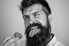 Gek over aardbei Mensen knappe hipster met lange baard die aardbei eten Hipster geniet van sappige rijpe rode bes Mens stock foto