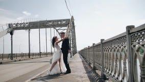 Gek paar van jonggehuwden met een paraplu in hun handen die op de rand van de brug dansen stock videobeelden
