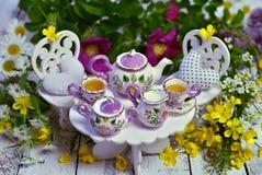 Gek theekransjeconcept met verfraaide kleine meubilair, koppen, theepot en bloemen op planken Stock Afbeeldingen