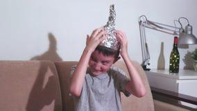 Gek zich vreemd gedraagt weinig jongen die met lelijke gezichtsuitdrukking tinfolie GLB, hoed dragen Hij gelooft dat het de herse stock footage