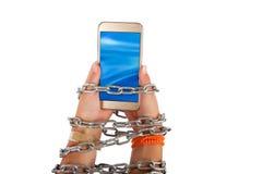 Geketende handen die een smartphone houden stock foto's