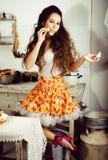 Gekke echte vrouwenhuisvrouw op keuken, die het perfoming eten, bizare Stock Fotografie