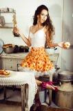 Gekke echte vrouwenhuisvrouw op keuken, die het perfoming eten, bizare Royalty-vrije Stock Afbeelding
