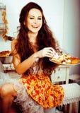 Gekke echte vrouwenhuisvrouw op keuken, die het perfoming eten, bizare Stock Afbeeldingen