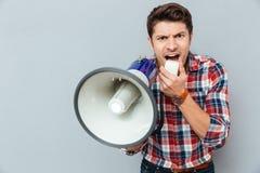 Gekke gekke jonge mens in plaid het korte schreeuwen in megafoon stock afbeelding