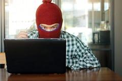 Gekke gemaskeerde hakker die balaclava met sleutel in handen dragen die gegevens van laptop stelen Internet-misdaadconcept stock foto's
