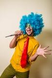 Gekke grappige jonge mens met blauwe pruik Stock Fotografie