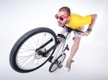 Gekke jongen op een fiets die van de vuilsprong grappige gezichten maken Stock Foto