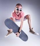 Gekke kerel die met een skateboard springen die grappige gezichten maken stock fotografie