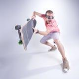 Gekke kerel met een skateboard die grappige gezichten maken Royalty-vrije Stock Foto's