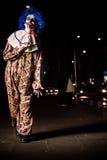 Gekke lelijke grunge kwade clown in stad op Halloween die mensenschok maken en doen schrikken Stock Foto's
