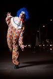 Gekke lelijke grunge kwade clown in stad op Halloween die mensenschok maken en doen schrikken Stock Afbeeldingen