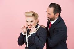 Gekke managers in kostuums en perls Het blonde en de werkgever in rode band hebben pret in studio met perls stock foto