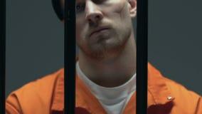 Gekke maniak met littekens op de gevangenis van de gezichtsholding bars en het gillen, geestelijke wanorde stock video