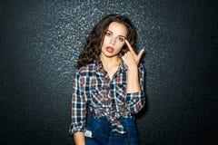 Gekke meisjespunten met haar vinger bij het hoofd Royalty-vrije Stock Foto's