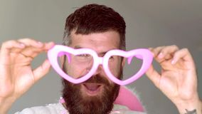 Gekke mens met grappige hipster roze zonnebril en grappige roze hoed Grappige hipstermens die camera over grijs bekijken stock videobeelden