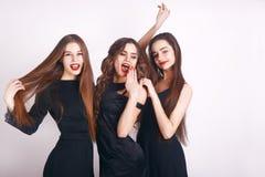 Gekke partijtijd van drie mooie modieuze vrouwen in het elegante avond toevallige zwarte kleding vieren, hebbend pret, het dansen stock fotografie