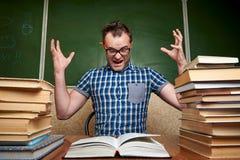 Gekke slordige vermoeide ongeschoren jonge mens die in glazen een boek lezen bij de lijst met stapels van boeken stock afbeeldingen