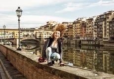Gekke vrouw die haar haar op de muur voor ponte v werpen Stock Afbeeldingen