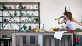 Gekke vrouw met gemberhaar die, in spatel in keuken zingen en voor camera stellen, vrolijk en gelukkig dansen stock videobeelden