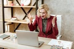Gekke woedende vrouw die op haar laptop tijdens aanval van agressie schreeuwen royalty-vrije stock foto's