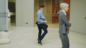 Gekke zakenman die met aktentas in moderne hal dansen terwijl zijn collega's die en verrast op hem lopen letten stock video