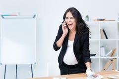 gekke zwangere onderneemster die terwijl het spreken schreeuwen stock afbeelding