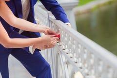 Geklede de jonggehuwden sluiten hart als teken van liefde Stock Afbeeldingen