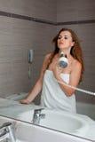 Gekleed in handdoek mooie vrouw die moeras gebruikt Stock Foto