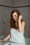 Gekleed in make-up van de handdoek de schitterende vrouw bij badkamers Stock Foto's