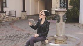 Gekleidete Frau der Junge modern schaut durch die Mitteilungen auf sozialen Netzwerken auf ihrer Tablette und lacht ausdrucksvoll stock footage