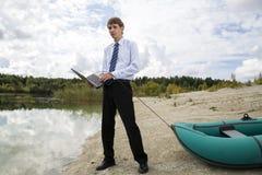 Gekleideter Mann schleppt Boot über Seeufer stockfotos