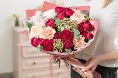 Gekleurd boeket van hoogst rood mooie luxebos van gemengde bloemen in de hand van de vrouw het werk van de bloemist bij a Stock Fotografie