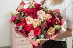 Gekleurd boeket van hoogst rood mooie luxebos van gemengde bloemen in de hand van de vrouw het werk van de bloemist bij a Stock Foto's