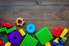 Gekleurd bouwspeelgoed voor kinderenmodel Legoblokken, minifigures op de donkere houten ruimte van het achtergrond hoogste mening Stock Afbeeldingen