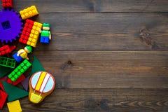 Gekleurd bouwspeelgoed voor kinderenmodel Legoblokken, minifigures op de donkere houten ruimte van het achtergrond hoogste mening Royalty-vrije Stock Foto's