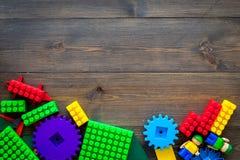 Gekleurd bouwspeelgoed voor kinderenmodel Legoblokken, minifigures op de donkere houten ruimte van het achtergrond hoogste mening Stock Foto's