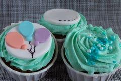 Gekleurd cupcakes close-up op grijze stoffenachtergrond stock foto's