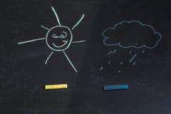 Gekleurd krijt, zwart bord met tekeningen van zon en een wolk Stock Foto