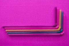 Gekleurd stro op een roze achtergrond stock afbeeldingen
