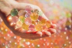 Gekleurde ballen van waterparels, hydrogel binnen in handen Sensorische expe stock fotografie