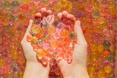 Gekleurde ballen van waterparels, hydrogel binnen in handen Sensorische expe stock afbeeldingen