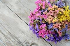 Gekleurde bloemen op houten textuur, bloemendecoratie royalty-vrije stock afbeelding