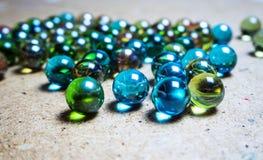 Gekleurde die glasballen op een houten oppervlakte worden verspreid stock foto's