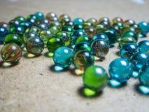 Gekleurde die glasballen op een houten oppervlakte worden verspreid stock afbeelding