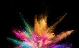 Gekleurde die poederexplosie op zwarte achtergrond wordt geïsoleerd Stock Fotografie
