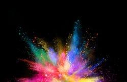 Gekleurde die poederexplosie op zwarte achtergrond wordt geïsoleerd Stock Afbeeldingen