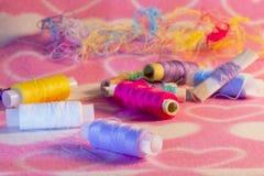 Gekleurde draad en naald op stof Stock Afbeeldingen
