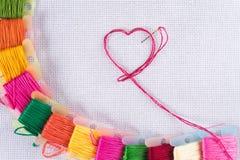 Gekleurde draad voor borduurwerk op wit canvas, een naald met rode draad in de vorm van een hart Het concept liefde voor een hobb royalty-vrije stock fotografie